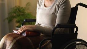 Mujer en la silla de ruedas que mira el álbum de foto, recordando momentos felices de la juventud metrajes