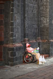 Mujer en la silla de ruedas que vende velas en la catedral en Banos, Ecuador Foto de archivo