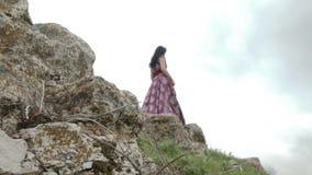 Mujer en la situación púrpura oscura del vestido en las rocas almacen de metraje de vídeo