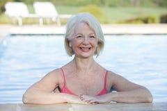 Mujer en la sonrisa al aire libre de la piscina Imagen de archivo