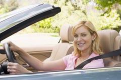Mujer en la sonrisa convertible del coche Imágenes de archivo libres de regalías