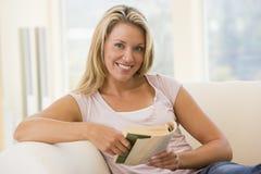 Mujer en la sonrisa del libro de lectura de la sala de estar Fotos de archivo