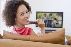 Mujer en la televisión de observación de la sala de estar Fotografía de archivo