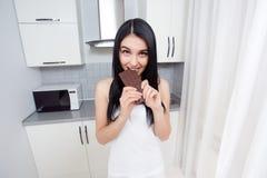 Mujer en la tenencia blanca por las manos y la consumición del chocolate oscuro fotos de archivo libres de regalías
