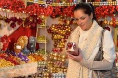 Mujer en la tienda de la decoración de la Navidad con las bolas Imagen de archivo