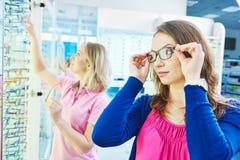 Mujer en la tienda de los vidrios del ojo Foto de archivo libre de regalías