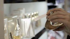 Mujer en la tienda que elige perfume con el papel metrajes