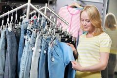 Mujer en la tienda que hace compras de los pantalones de los vaqueros Fotografía de archivo libre de regalías