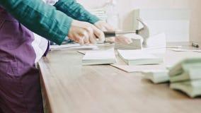 Mujer en la tipografía - complementos las páginas del folleto con un martillo en la industria del polígrafo, trabajo manual metrajes