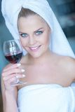 Mujer en la toalla de baño blanca que sostiene el vidrio de vino Imagen de archivo