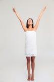 Mujer en la toalla que se coloca con las manos aumentadas para arriba Fotos de archivo