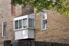 Mujer en la ventana, el agitar, sonriendo Fotos de archivo