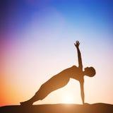 Mujer en la yoga lateral de la balanza que medita en la puesta del sol zen Foto de archivo