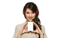 Mujer en las auriculares que sostienen la tarjeta de visita vacía Fotografía de archivo libre de regalías