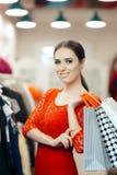 Mujer en las compras rojas del vestido del cordón para la ropa Fotos de archivo
