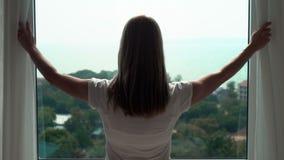 Mujer en las cortinas blancas de la revelación de la camiseta y mirada fuera de ventana Disfrutando de la opinión del mar afuera almacen de metraje de vídeo