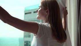 Mujer en las cortinas blancas de la revelación de la camiseta y mirada fuera de ventana Disfrutar de la opinión del mar fuera de  almacen de video