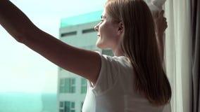 Mujer en las cortinas blancas de la revelación de la camiseta y mirada fuera de ventana Gozando del mar vea 100 fps metrajes