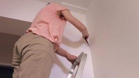 Mujer en las escaleras que pintan la esquina de la pared almacen de video