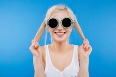 Mujer en las gafas de sol que miran la cámara Fotos de archivo