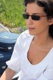 Mujer en las gafas de sol que se sientan al lado de sus maletas Imágenes de archivo libres de regalías