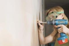 Mujer en las gafas protectoras que perforan la pared imagenes de archivo