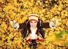 Mujer en las hojas anaranjadas del otoño, al aire libre Fotos de archivo libres de regalías