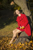 Mujer en las hojas del parque y del amarillo del otoño Imagen de archivo