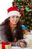 Mujer en las manoplas del sombrero y de la piel de Papá Noel que mienten debajo del árbol de navidad Imagenes de archivo