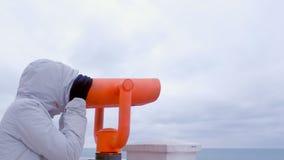 Mujer en las miradas blancas de la chaqueta y de la capilla en prismáticos en la costa del mar con la opinión del mar Vista later almacen de video