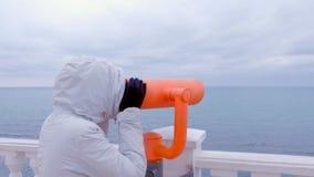 Mujer en las miradas blancas de la chaqueta y de la capilla en prismáticos en la costa del mar con la opinión del mar Vista later metrajes