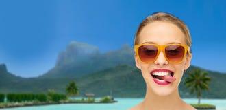 Mujer en las sombras que muestran la lengua sobre la playa del verano Foto de archivo libre de regalías