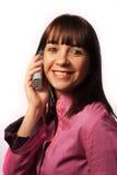 Mujer en las sonrisas del teléfono Imagen de archivo libre de regalías