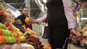 Mujer en las verduras y las frutas de compra del mercado almacen de metraje de vídeo