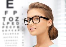 Mujer en lentes con la carta de ojo Imagenes de archivo