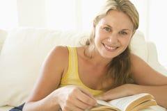 Mujer en libro de lectura de la sala de estar Fotografía de archivo libre de regalías