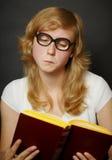 Mujer en libro de lectura pasado de moda divertido de los vidrios Foto de archivo
