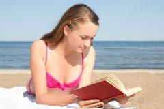 Mujer en libro de lectura rosado del bikini en la playa Fotografía de archivo