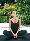 Mujer en los auriculares que hacen la yoga rt Imagenes de archivo