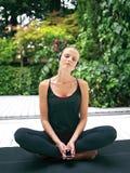 Mujer en los auriculares que hacen ri de la yoga Foto de archivo