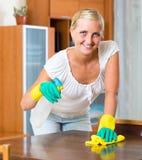 Mujer en los guantes de goma que limpian dentro Imagenes de archivo