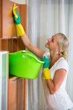 Mujer en los guantes de goma que limpian dentro Fotos de archivo