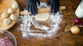 Mujer en los guantes negros que ruedan la pasta con el rodillo para hacer la pizza o la empanada almacen de metraje de vídeo