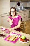Mujer en los pijamas que tienen pulgar del desayuno para arriba Fotografía de archivo