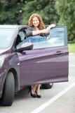 Mujer en los tacones altos que se colocan cerca de un nuevo coche Foto de archivo