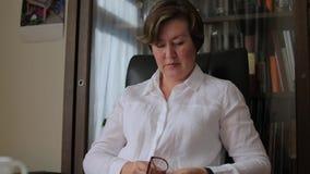 Mujer en los vidrios blancos de las frotaciones de la camisa metrajes