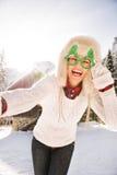 Mujer en los vidrios de la Navidad que toman el selfie cerca de una casa de la montaña Fotos de archivo