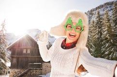Mujer en los vidrios de una Navidad que toman el selfie cerca de una casa de la montaña Fotografía de archivo libre de regalías