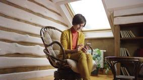 Mujer en los vidrios que mandan un SMS en smartphone en ático almacen de metraje de vídeo