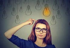 Mujer en los vidrios que miran para arriba con el bulbo ligero de la idea sobre la cabeza Foto de archivo libre de regalías